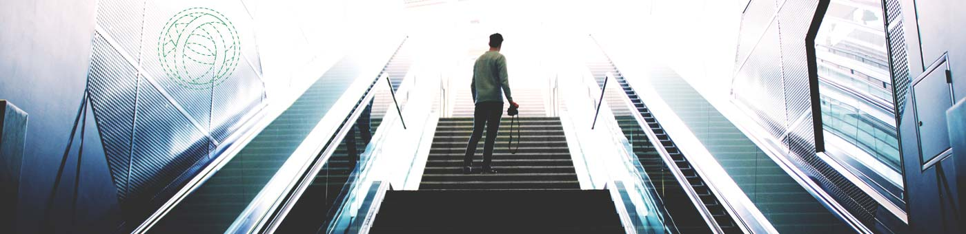 A person ascends towards the light on an escalator; because enlightenment.