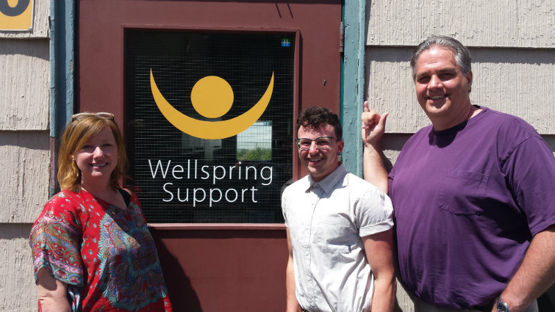Nicole Funk, ED of Wellspring, and Stephen Twynstra, Program Director, stand with Kingsley in front of a red door showing the yellow Wellspring logo.