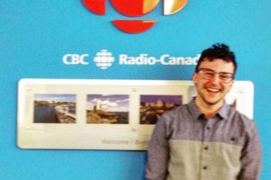 Kingsley stands to the left of the red CBC symbol at the CBC on the Island Radio station.