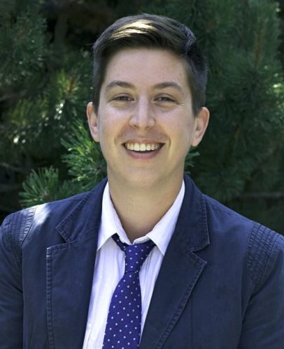 Julian, a white trans-masculine person stand outside in front of some bushes. He is smiling and wearing a black suit, white shirt, and a purple tie. He is flipping a page in an old book.