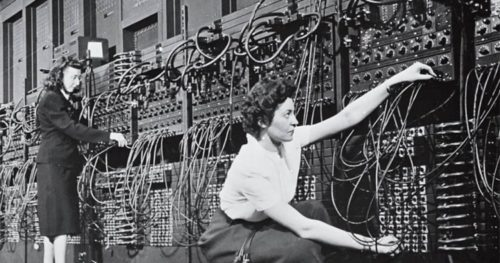 Two women in the 1950's, connecting circuits on a huge computer. Photo is in black and white