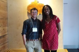Kingsley poses with Dr. Lisa Gunderson, who has long dark hair and is wearing a red dress.