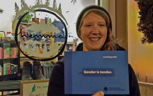 Alison hold up a postcard that says 'Gender is Tender' outside the doors of hemma