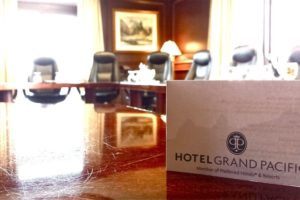 A business card that says Hotel Grand Pacific sits on a large wooden table in a conference room. In the background are 5 office chairs that are around the table.