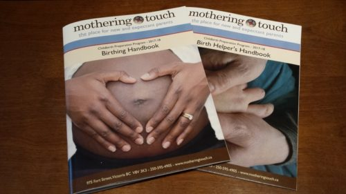 A birthing handbook and a birth helpers handbook. The handbook has a picture of two hand on a pregnant belly.