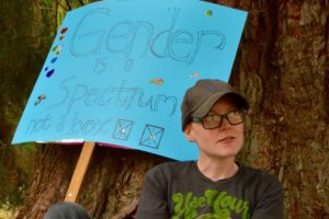 Quinn Hiebert, a gender non-conforming white person sits in front of a large cedar tree with a blue sign that reads Gender Is Not A Spectrum. Quinn is wearing a black ball cap and a black t-shirt with green cursive writing
