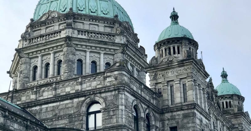 A photo of the green peaks of the BC Legislature buildings, with a grey sky in the background.