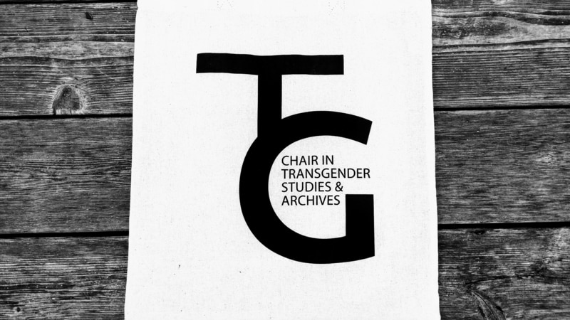 "Tote bag that reads ""TG Chair in Transgender Studies"" on a wooden background."