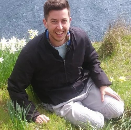 Julian, a white trans-masculine person stand outside in front of some bushes. He is smiling and wearing a black sweater and khaki pants. He is kneeling on grass with water in the background