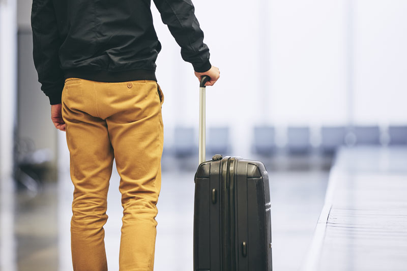 A business person, a speaker, is in an airport ready to travel for work.